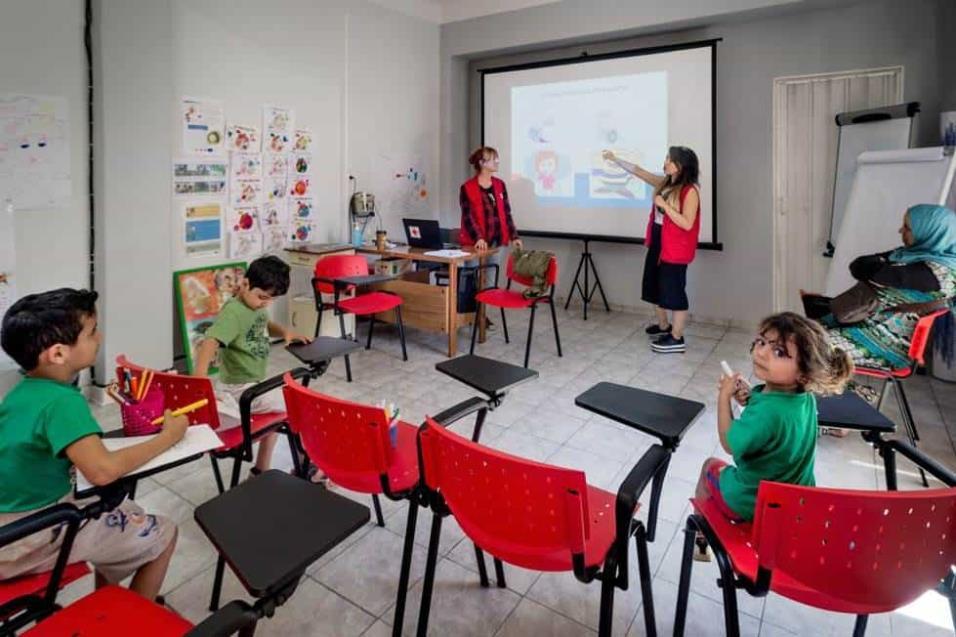 Dos trabajadoras de Cruz Roja imparten clases a menores refugiados en el ambulatorio de Ambelokipi, en Atenas. ANGEL LOPEZ SOTO