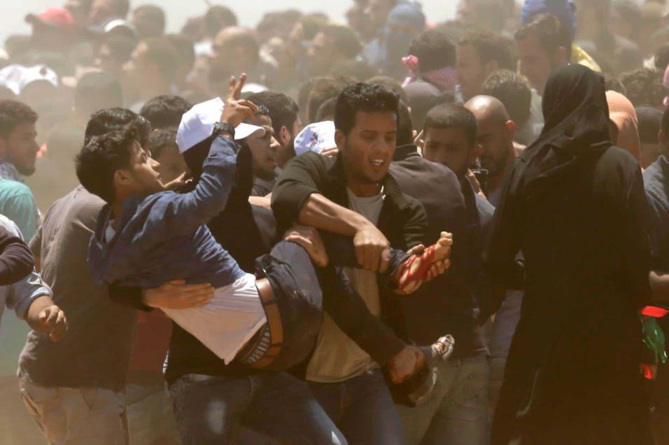 Palestinos trasladan a un herido durante los choques en la franja de Gaza, el 14 de mayo de 2018. MAHMUD HAMS AFP