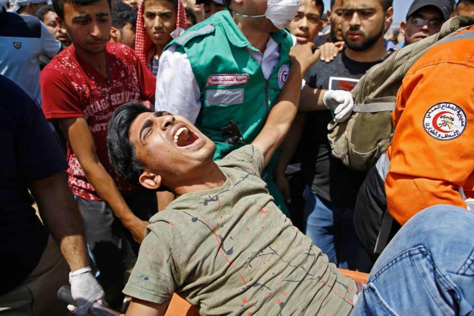 Personal de emergencias trasladan a un herido durante los enfrentamientos con las fuerzas de seguridad israelíes en la frontera entre Gaza e Israel, el 14 de mayo de 2018. MOHAMMED ABED AFP