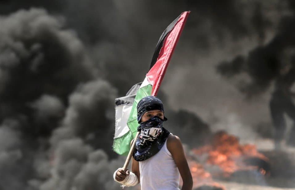 Un niño sujeta la bandera de Palestina durante los enfrentamientos en la franja de Gaza, el 14 de mayo de 2018. MAHMUD HAMS AFP