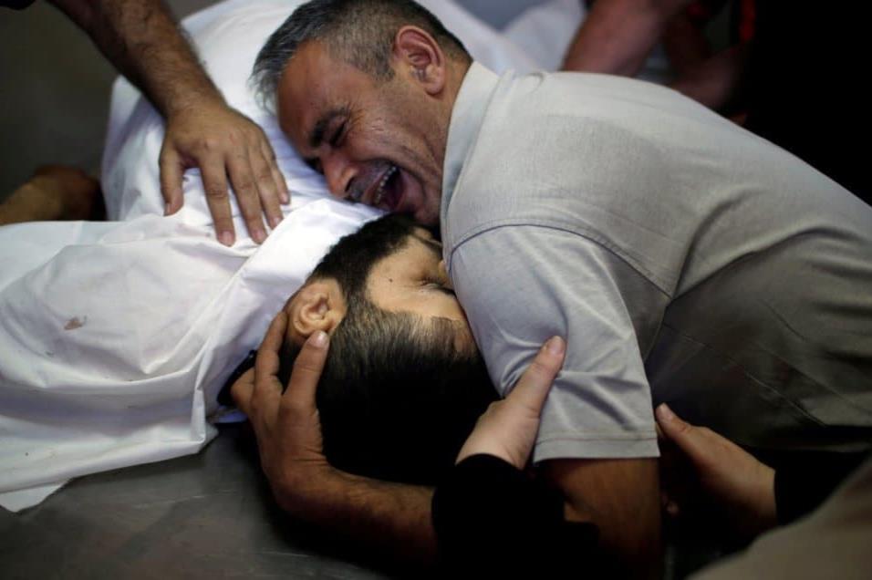 Shaher al-Madhoon, que murió durante la protesta en la frontera entre Israel y Gaza, y su hermano que reacciona por encima de su cuerpo en la morgue de un hospital en el norte de la franja de Gaza el 14 de mayo de 2018. MOHAMMED SALEM REUTERS