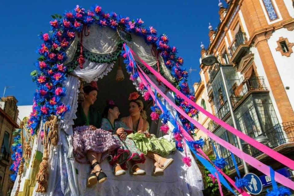Tres mujeres subidas en una carreta en la salida de la Hermandad de El Rocío de Triana del popular barrio sevillano esta mañana hacia la aldea de El Rocío. JULIO MUÑOZ EFE