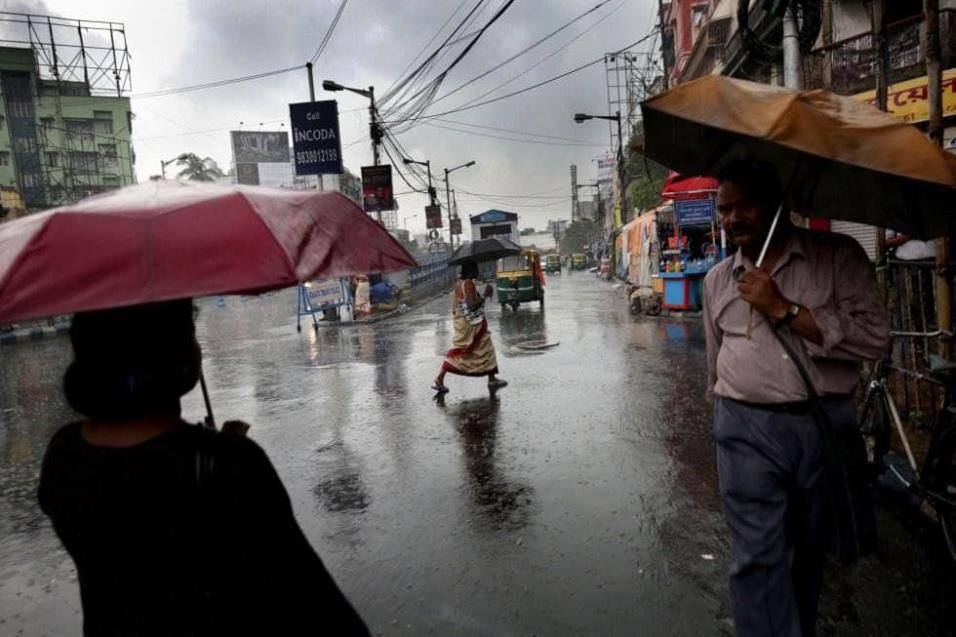 Varias personas caminan bajo la fuerte lluvia, en Calcuta (India). PIYAL ADHIKARY EFE