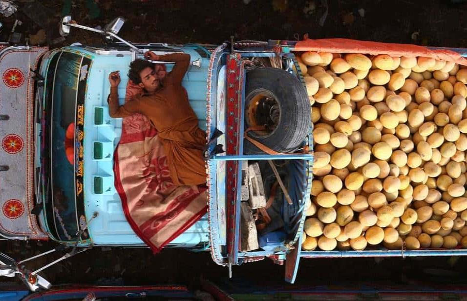 Un vendedor se echa una siesta en su furgoneta donde vende melones en un mercado en Karachi (Pakistán). SHAHZAIB AKBER EFE
