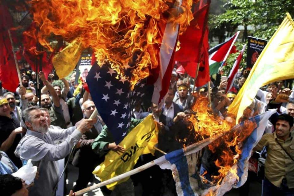 Iraníes queman las banderas de Israel y Estados Unidos durante una protesta dentro de la antigua embajada estadounidense, en Teherán (Irán). EBRAHIM NOROOZI AP