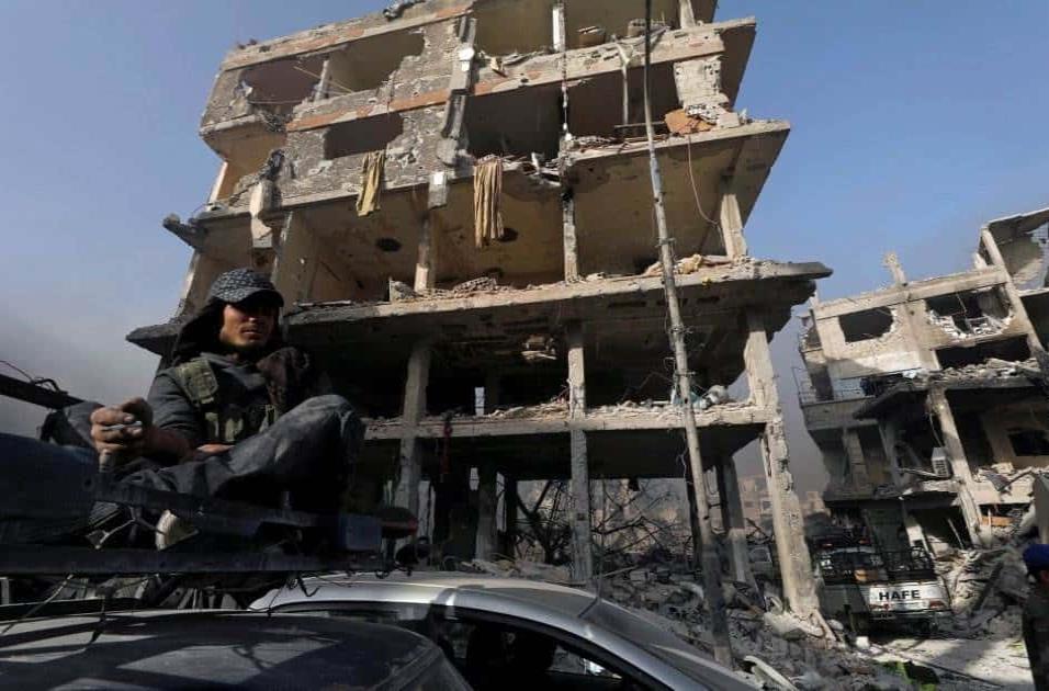 Un soldado del Ejército sirio se fuma un cigarro frente a un edificio en escombros en al-Hajar al-Aswad, el 21 de mayo de 2018. OMAR SANADIKI REUTERS