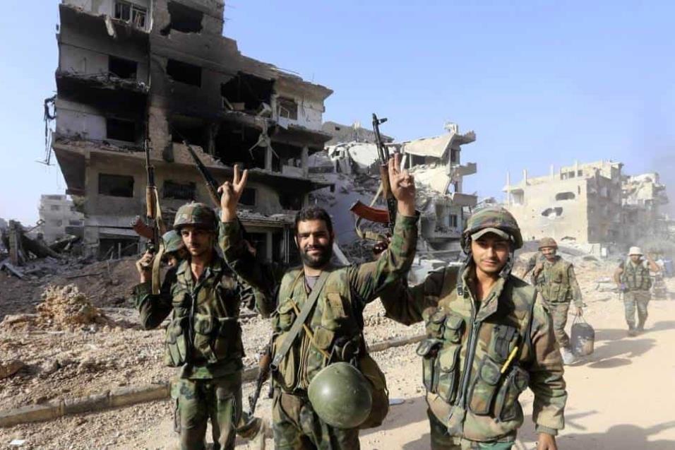 Soldados del Ejército sirio gesticulan a cámara mientras caminan entre los escombros del campo palestino de Yarmuk, a las afueras de Damasco, el 21 de mayo de 2018. LOUAI BESHARA AFP