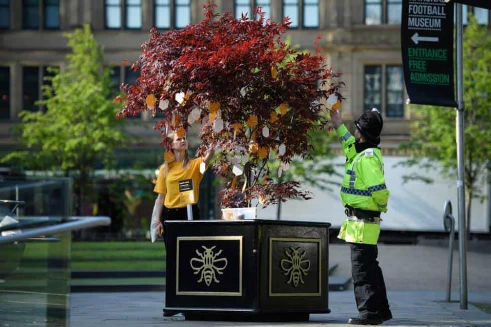 Un agente de policía se acerca al árbol de la esperanza, donde numerosas personas han dejado mensajes en recuerdo a las víctimas de la tragedia del 22 de mayo de 2017 en Manchester cuando 22 personas murieron tras un atentado al salir de un concierto de