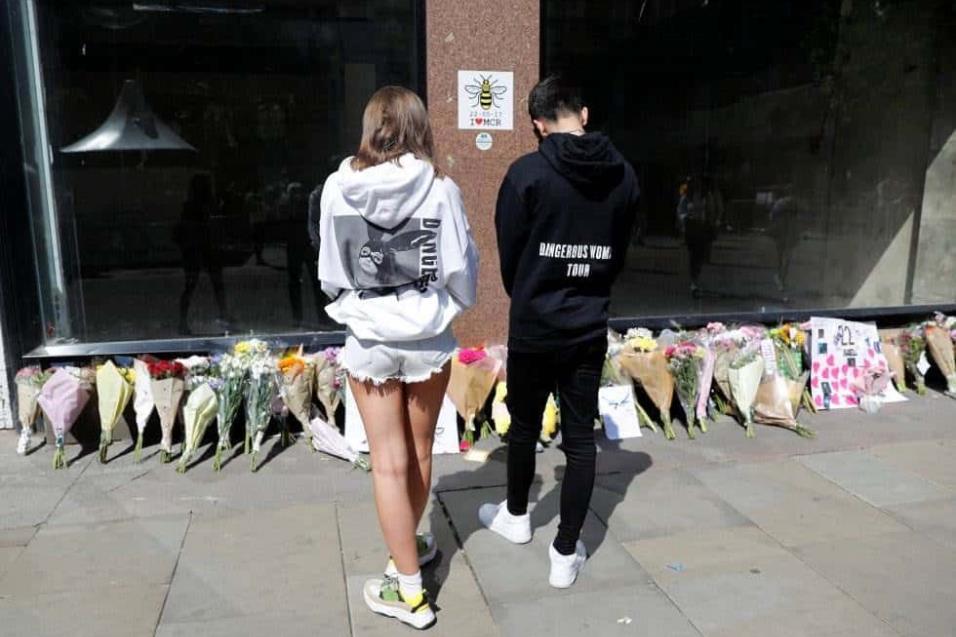 Dos jóvenes con sudaderas de Ariana Grande dejan flores en la plaza de Santa Ana en Manchester, en el primer aniversario del atentado en el Manchester Arena. DARREN STAPLES REUTERS