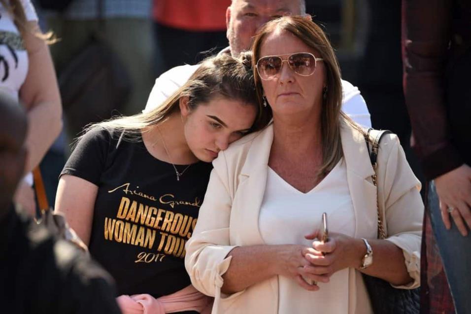Una mujer con la camiseta de Ariana Grande reacciona frente a la Catedral de Manchester. OLI SCARFF AFP